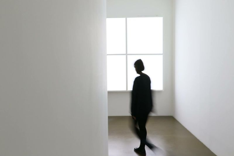 Blurred motion of woman walking in hallway with white wall