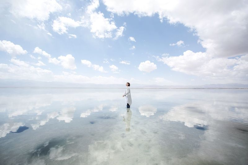 Reflection Of Cloudy Sky And Woman On Sea