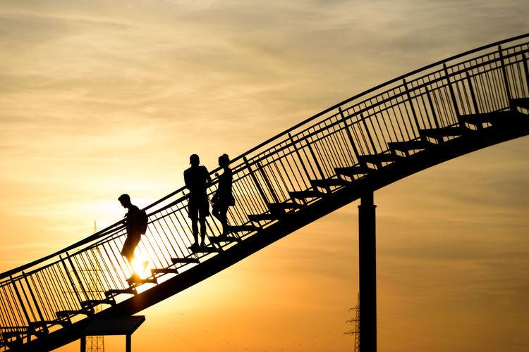 Silhouette people on footbridge against sky