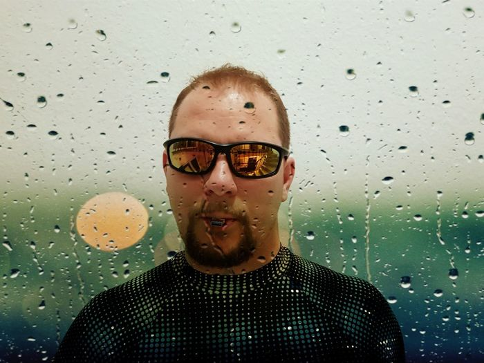 Portrait of a smiling man in rain