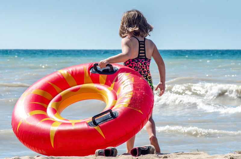 A young girl kicks off her sneakers, and gets ready to take her floating toy into the lake