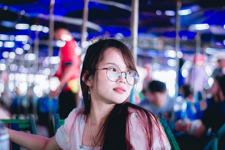 Smiling young woman wearing eyeglasses looking away while standing outdoors at night