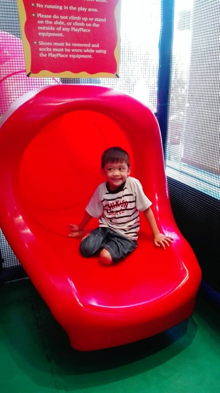 childhood, real people, front view, red, one person, looking at camera, playing, sitting, indoors, cute, portrait, leisure activity, full length, happiness, day, smiling, people