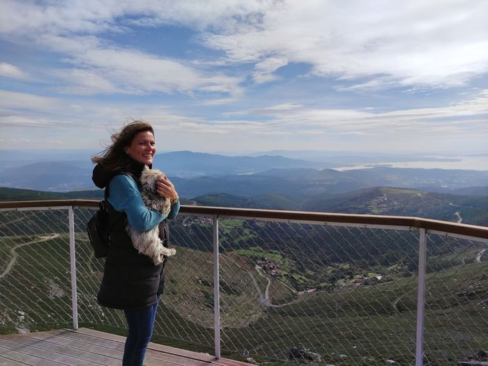 Full length of woman standing on railing against mountain