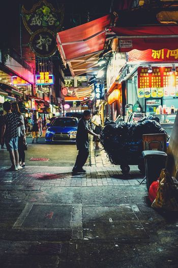 Reframinghk Discoverhongkong Streetphotography Nightshooters Artisanandartist City Street Night Architecture Building Exterior Illuminated City Life Real People Built Structure Motor Vehicle Wet Group Of People Road Women Lifestyles Transportation City Street Walking People Outdoors