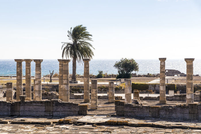 Ruins of Baelo Claudia, an ancient Roman town outside of Tarifa, near the village of Bolonia, in Andalusia, southern Spain Architecture Baelo Claudia Bolonia Spain Palm Tree Roman Ruins Ruins Architectural Column Beach Blue Sky Horizon Horizon Over Water Temple