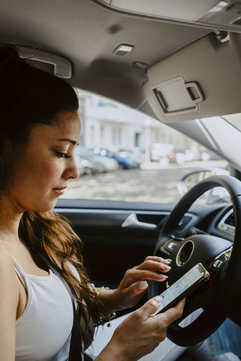 Side view of woman using mobile phone in car
