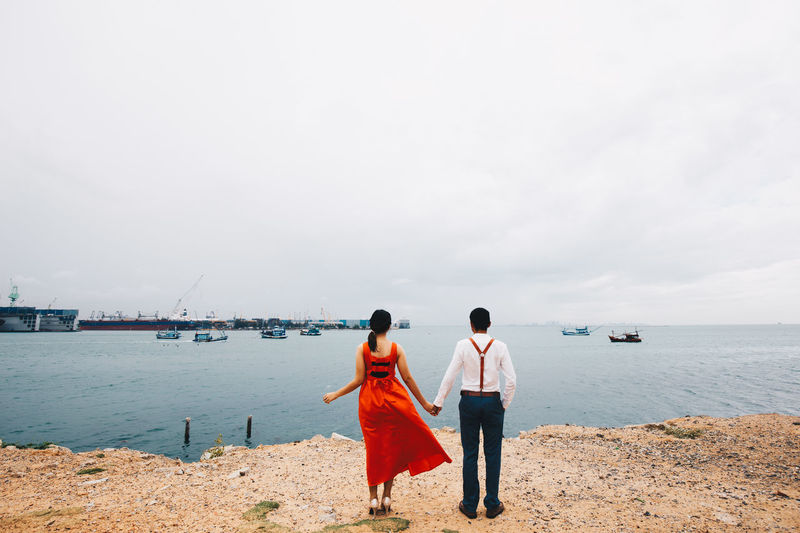 Rear view of couple holding hands while standing at beach against cloudy sky
