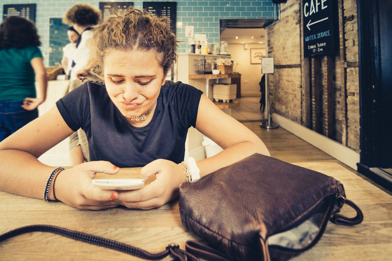 Girl reading bad news on her smartphone with a disgusted face sitting in a hipster cafe. Bad News Bag Cafe Casual Clothing Caucasian Cellphone Creamy Disgruntled Disgusted Disgusted Face Friends Girl Hipster Holding Indoors  Lifestyles Phone Photography Real People Smartphone Texting Unhappy Weird Face Young Adult Young Women
