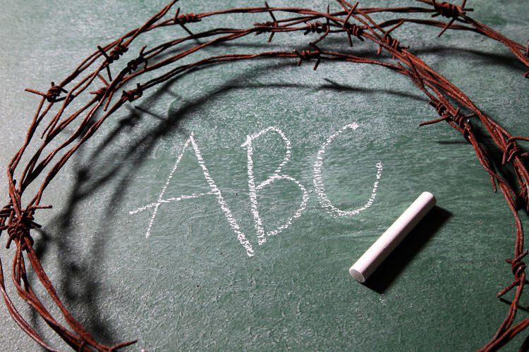 Close-Up Of Rusty Barbed Wire With Chalk On Blackboard