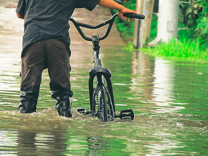 Low section of man with bicycle in water