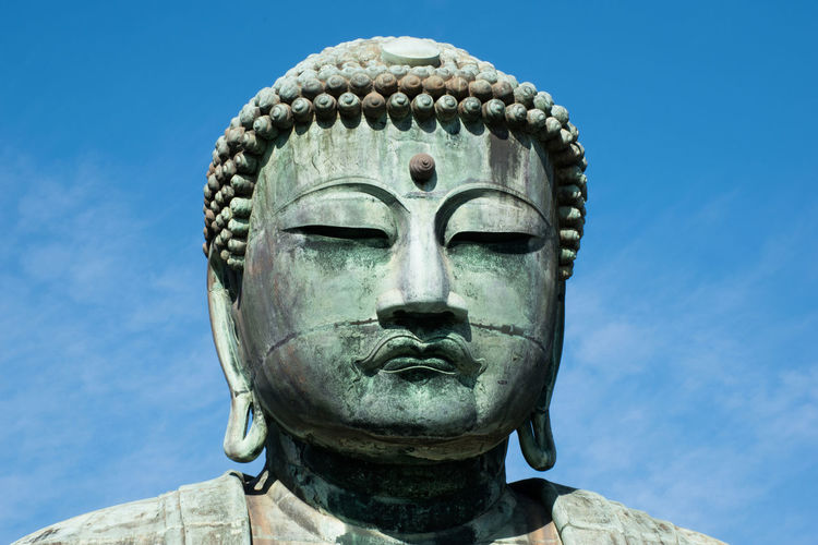 Close-up of statue against blue sky