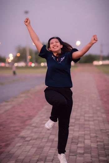 Full length of cheerful young woman dancing on footpath at sunset