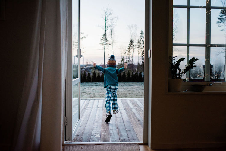 Rear view of boy standing by window at home
