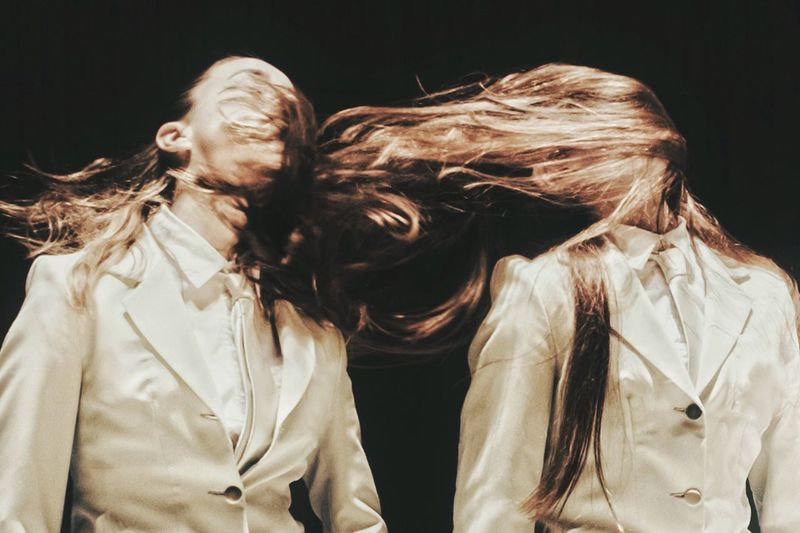 Multiple image of woman tossing hair against black background