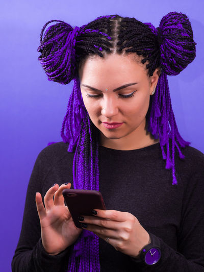Adorable hipster caucasian female with african colorful braids hairstyle checking news feed or messaging via social networks, using free wi-fi on mobile phone, smiling, posing on violet wall African Hairstyle African Braids Beautiful Woman Blue Close-up Communication Day Front View Holding Indoors  Leisure Activity Lifestyles Looking Down Mobile Phone One Person People Portable Information Device Purple Real People Smart Phone Technology Text Messaging Wireless Technology Young Adult Young Women