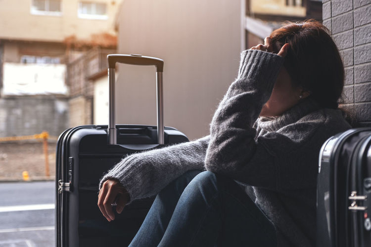 woman feel stressed and lost while traveling Women Travel Traveler Headache Stressed Lost Sad Cry Feeling Bag Baggage Luggage Street Tired Asian  Tourist Journey Real People One Person Sitting Lifestyles Leisure Activity Casual Clothing
