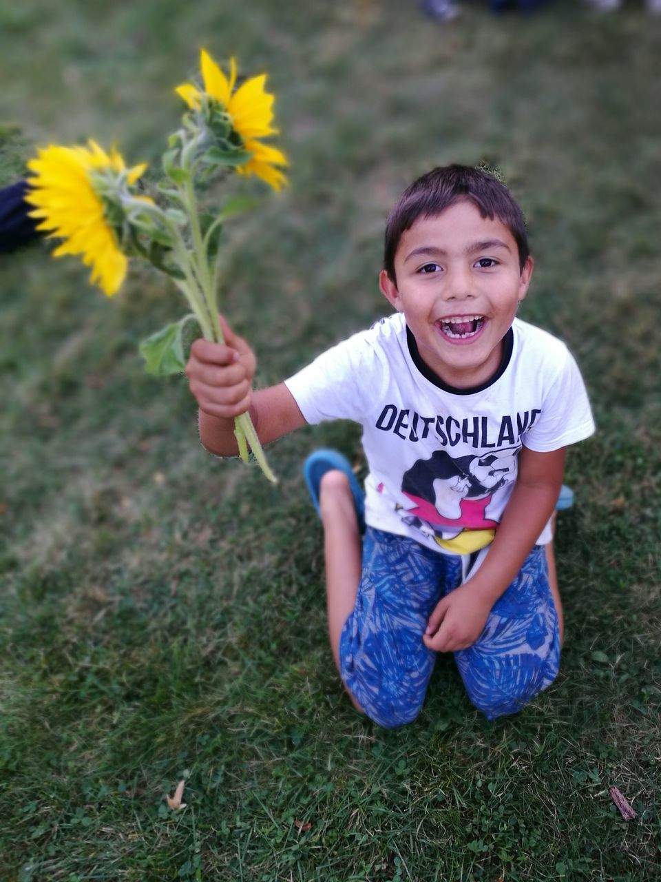 flower, childhood, one person, real people, looking at camera, girls, smiling, field, front view, portrait, happiness, casual clothing, holding, elementary age, child, lifestyles, boys, day, leisure activity, outdoors, cheerful, grass, nature, growth, freshness, fragility, human hand, people