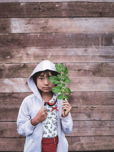 Portrait of girl holding plant standing against wooden wall outdoors