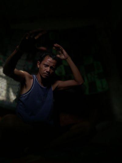 Man gesturing while sitting in darkroom