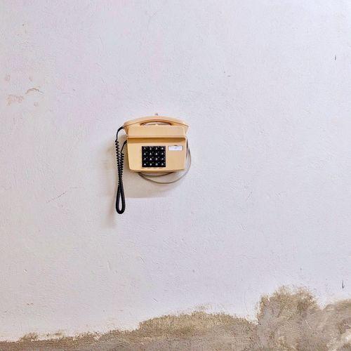 Landline phone hanging on white wall