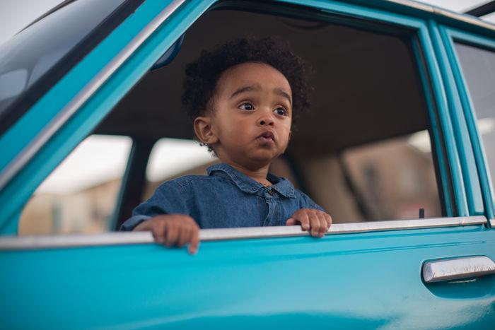 Portrait of young boy in car window