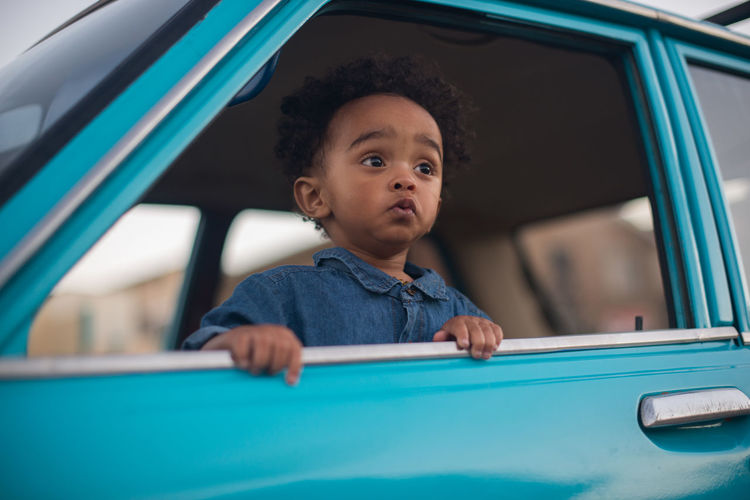 Portrait of young boy in car window