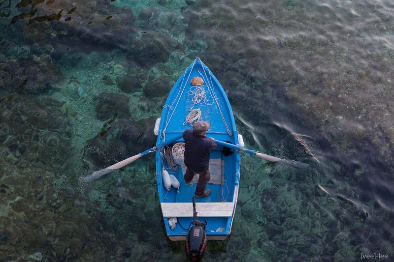 High angle view of man sitting on boat in sea