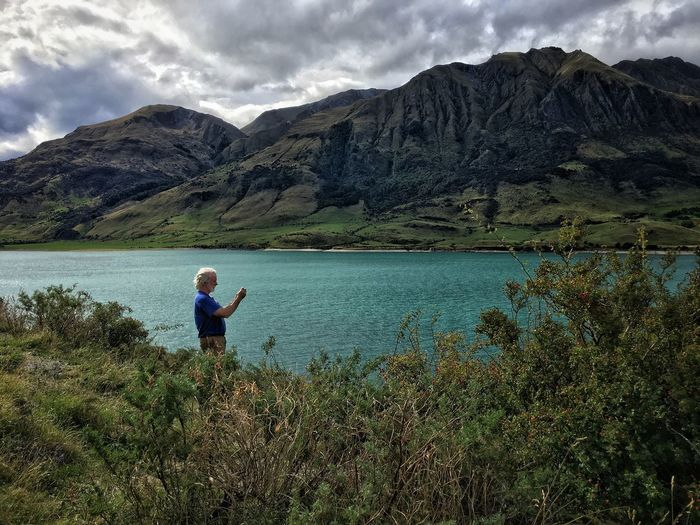 Man standing at lakeshore against mountains