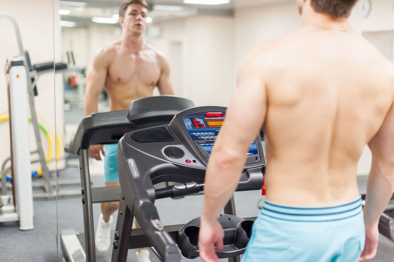 Shirtless young man on treadmill reflecting on mirror in gym