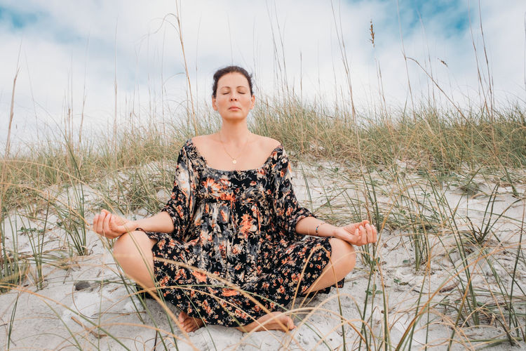 Beautiful woman meditates in boho dress with closed eyes on a sandy beach against nature background.