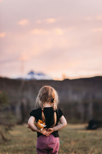 Girl standing on field against sky during sunset