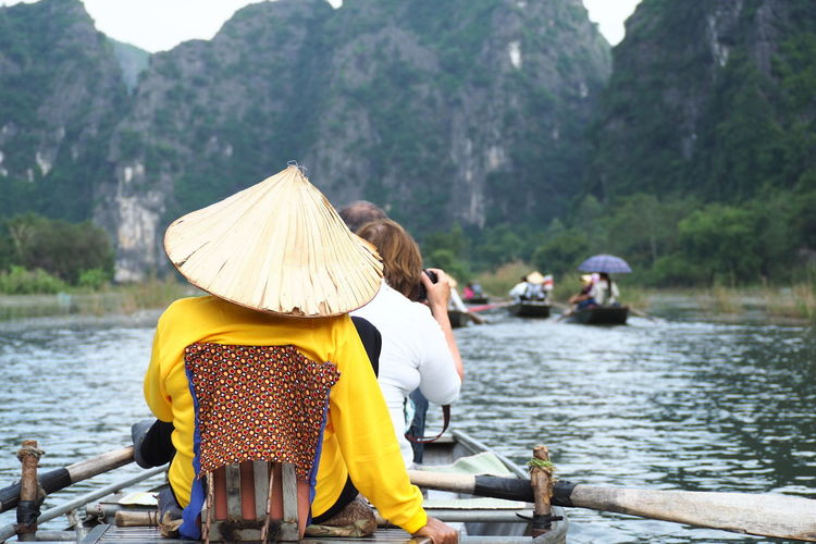 River Boat Ride at Tam Coc River and caves in Hanoi, Vietnam. The 1.5 hour long river boat ride has forced peddlers to adapt and use their legs to row the boats instead, making it less taxing on their body. Asian Style Conical Hat Boat Cultures Day Eco Tourism EyeEm Best Shots EyeEm Street Photography Hat Mountain Nature Outdoors Peddler People Rear View River Riverbank Sampan Tam Coc Travel Travel Destinations Vacations Vietnam Water Women Enjoy The New Normal The Great Outdoors - 2017 EyeEm Awards The Street Photographer - 2017 EyeEm Awards