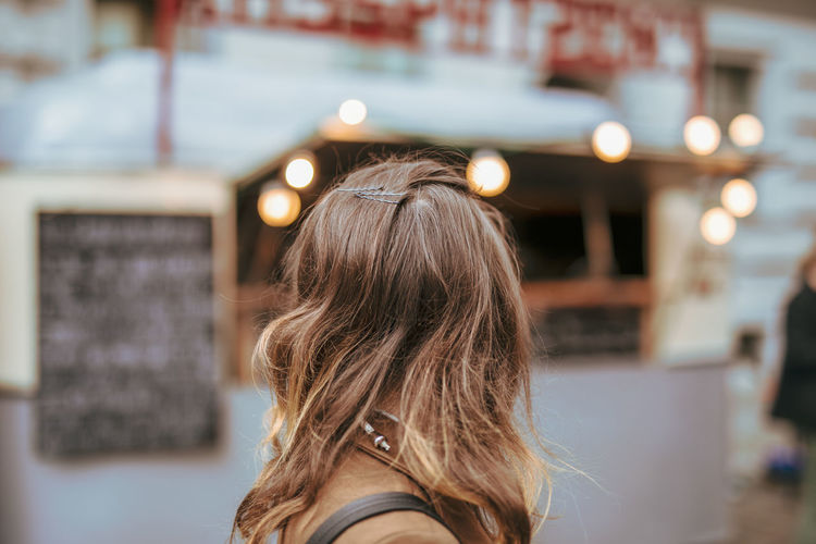 Side view of woman with brown hair in city