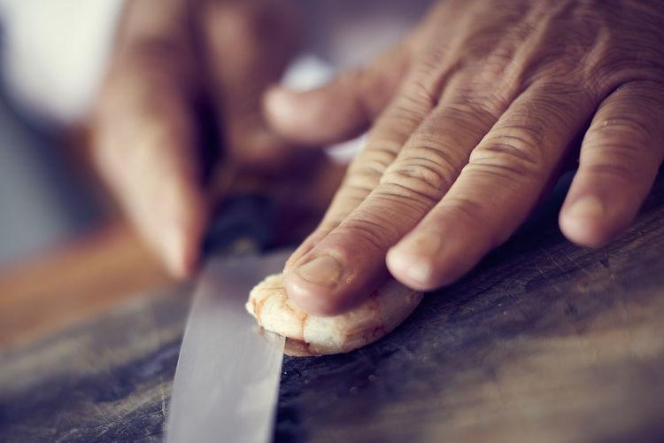 Close-up of hand cutting shrimp