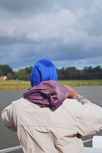 Rear view of man with umbrella against sky