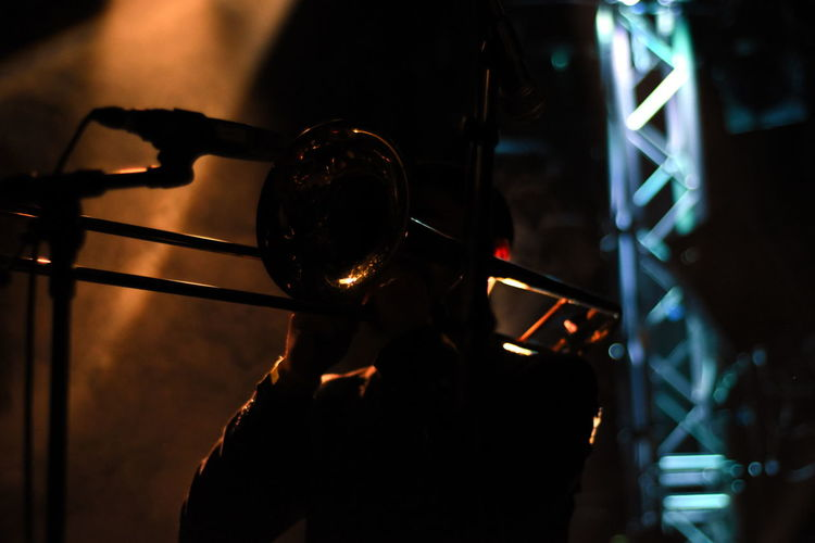 Silhouette person playing trumpet at music concert