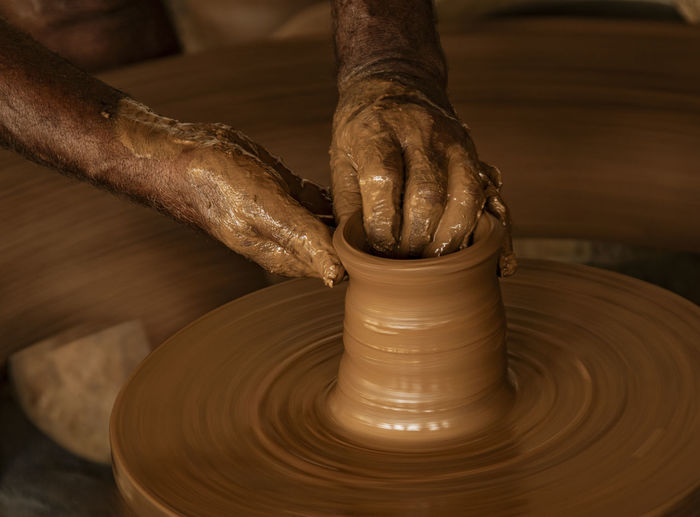 Cropped hands making pot