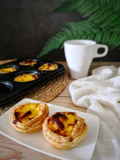 Portugese egg tart with a cup of tea Portugese Egg Tarts Egg Tart A Cup Of Tea Foodphotography Foodstyling Foodphotography Foodstyling Soft Focus Plate Close-up Sweet Food Food And Drink Tart - Dessert Pastry Dough Baked Pastry Item Puff Pastry Baked