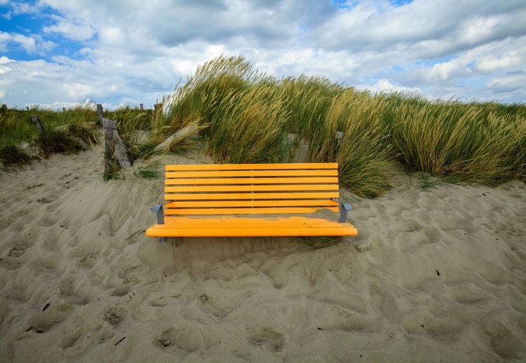 Empty seats on sand at beach against sky