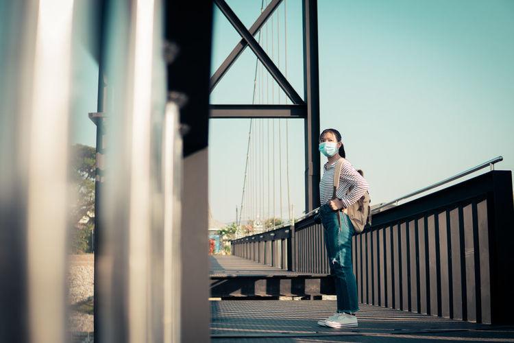 Man standing by railing on bridge against sky