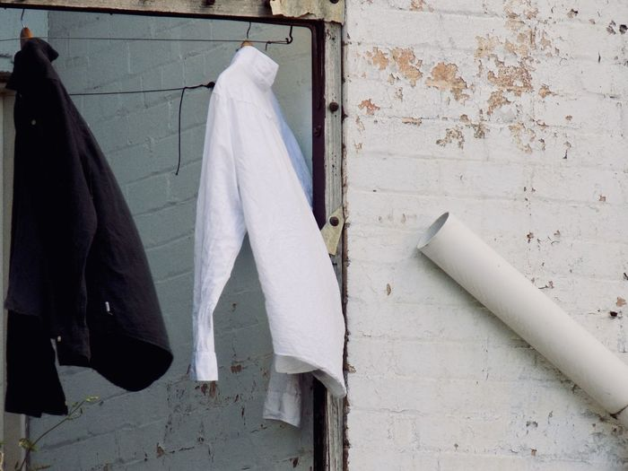 Close-up of clothes drying against white wall