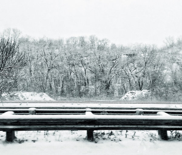 Railroad track by trees against clear sky during winter