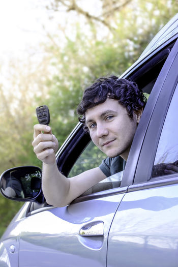 Portrait of young man looking through car window while holding key
