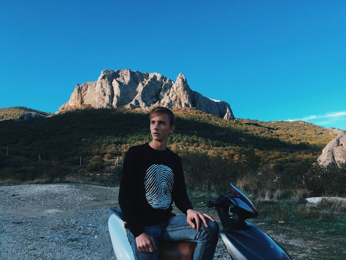 Man sitting on motorcycle against mountains