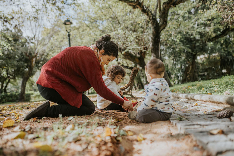 Mother playing outdoors with two children