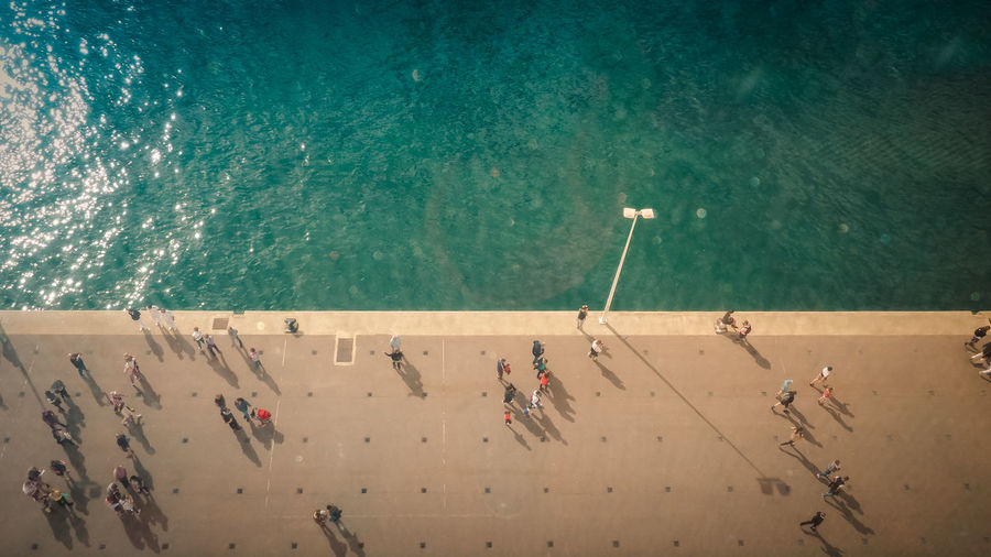 High angle view of people walking on promenade by sea
