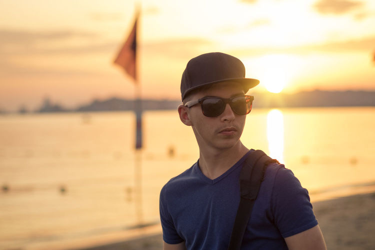 Young man wearing sunglasses standing against sea during sunset
