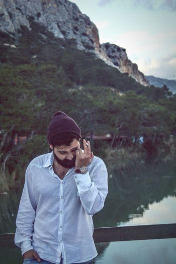 Man smoking cigarette against lake