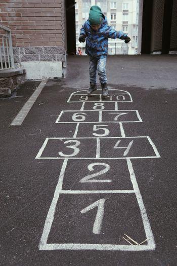 Boy Playing Hopscotch On Street
